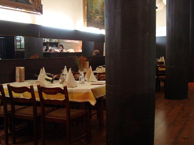 """Ресторан """"Зона Замфирова"""". Зал рядом с барной стойкой с сервированными столами"""